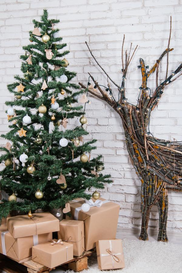 New Year`s location in the studio with a deer, decorated with a Christmas tree, gifts, a basket of cones stock photography