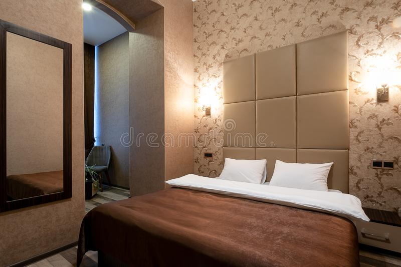 Room with a double bed,bedside table,mirror on the wall,white door,beige walls,laminate flooring and a passage to the bathroom and. Hallway.On each side of the royalty free stock images