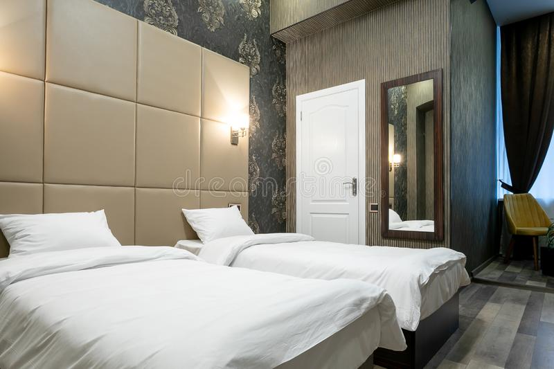 Room with a double bed,bedside table,mirror on the wall,white door,window with curtains,laminate flooring and a passage to the bat. Hroom and hallway.On each royalty free stock images
