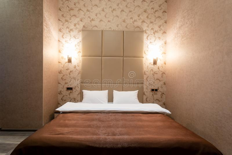 Room with a double bed, bedside table, and a white door, gray walls and laminate flooring. On each side of the bed on the wall lam stock photography