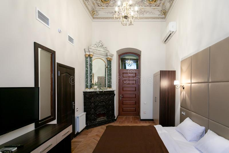 Room with a double bed, TV, mirror on the wall, vintage fireplace, laminate floor, access to the bathroom and hallway, with hand-p. Ainted ceiling and crystal stock images