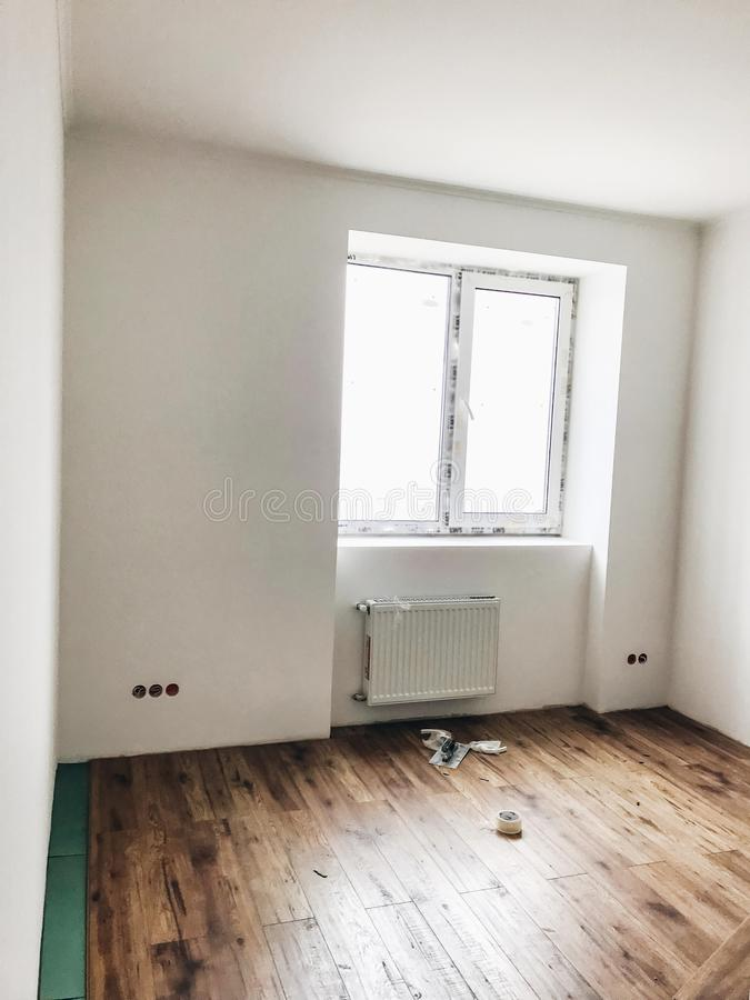 Room floor renovation concept. stylish wooden laminate instalation, modern white walls. repairing and working in home, space for. Text. hardwood plank parquet royalty free stock images