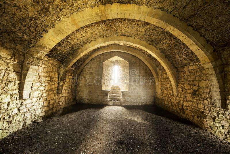 Room inside old castle. Room inside an old castle with a window cell and archways stock photo