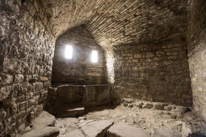Room inside old castle. Room inside an old castle with a window cell and archways stock photography