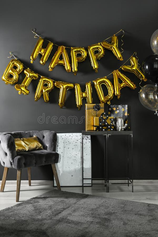 Room interior with gift boxes and phrase HAPPY BIRTHDAY made of balloon letters royalty free stock images