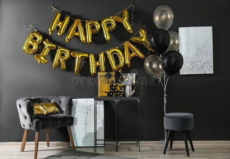 Room interior with gift boxes and phrase HAPPY BIRTHDAY made of balloon letters royalty free stock image
