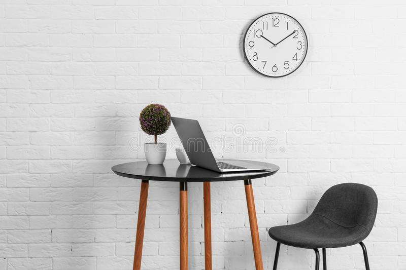 Room interior with table and analog clock hanging stock image