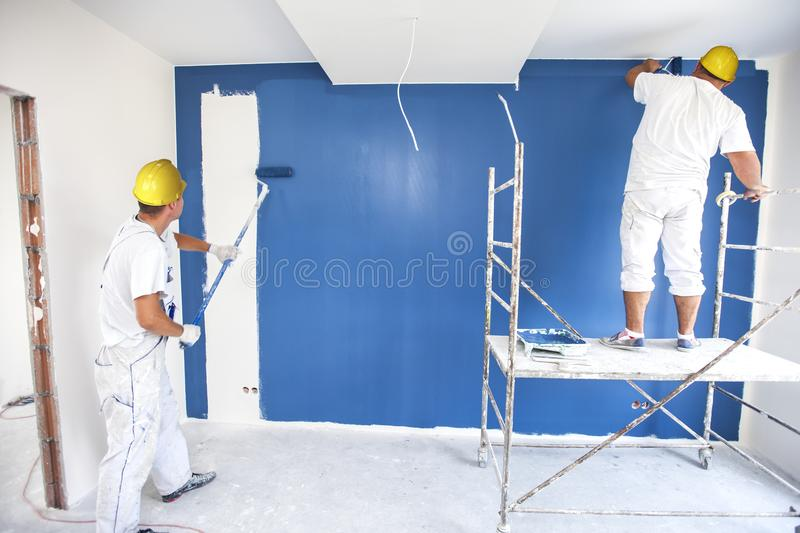 Room painter paints a wall in a new home. stock photography