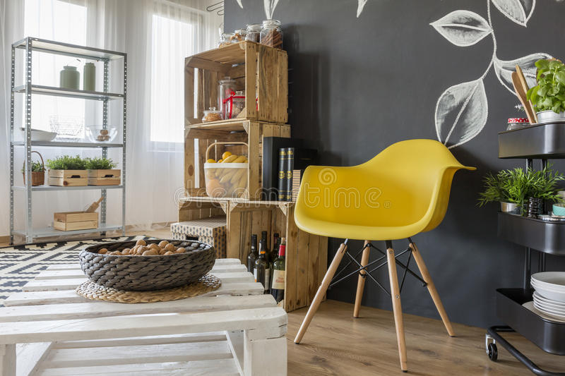 Room with pallets furniture. Blackboard and yellow chair stock images