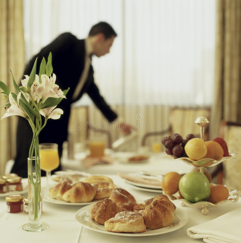 Room service continental breakfast. Big Hotel room service continental breakfast with waitress out of focus royalty free stock image