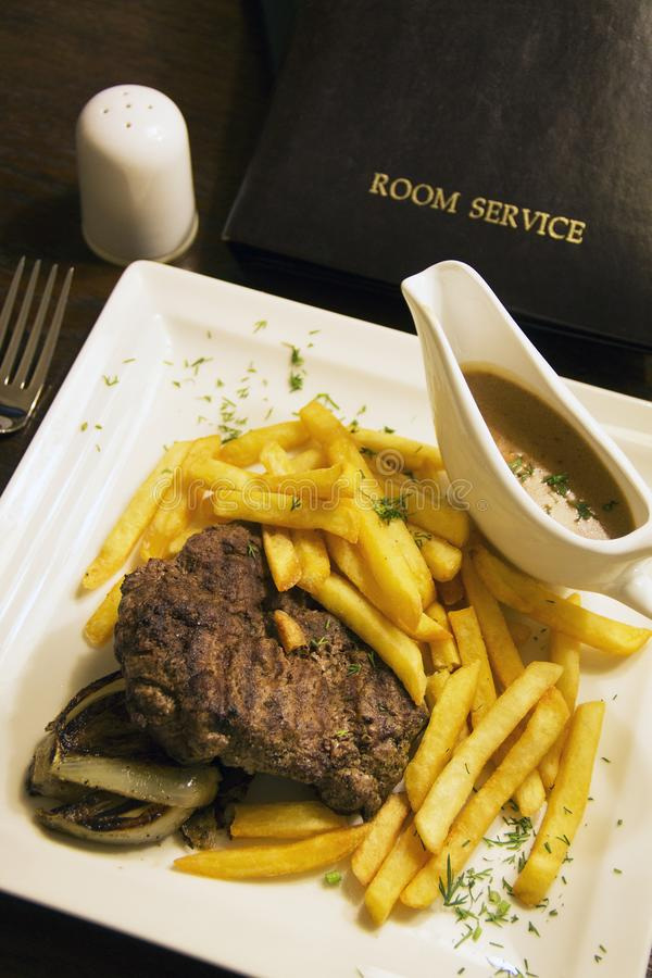Room service. Mignon of beef and French fries with nut sauce. Close-up stock image