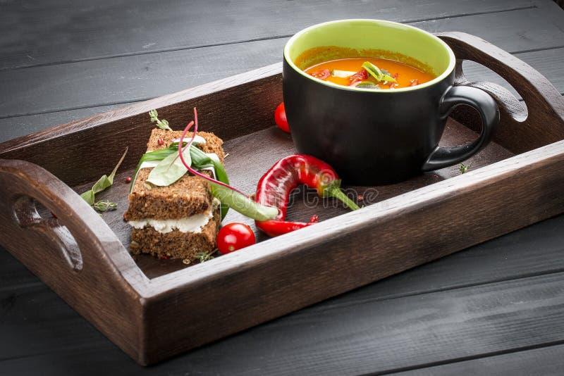 Room-soep van tomaten en gebakken peper, met een multi-korrelbrood met gerookte suluguni royalty-vrije stock afbeeldingen