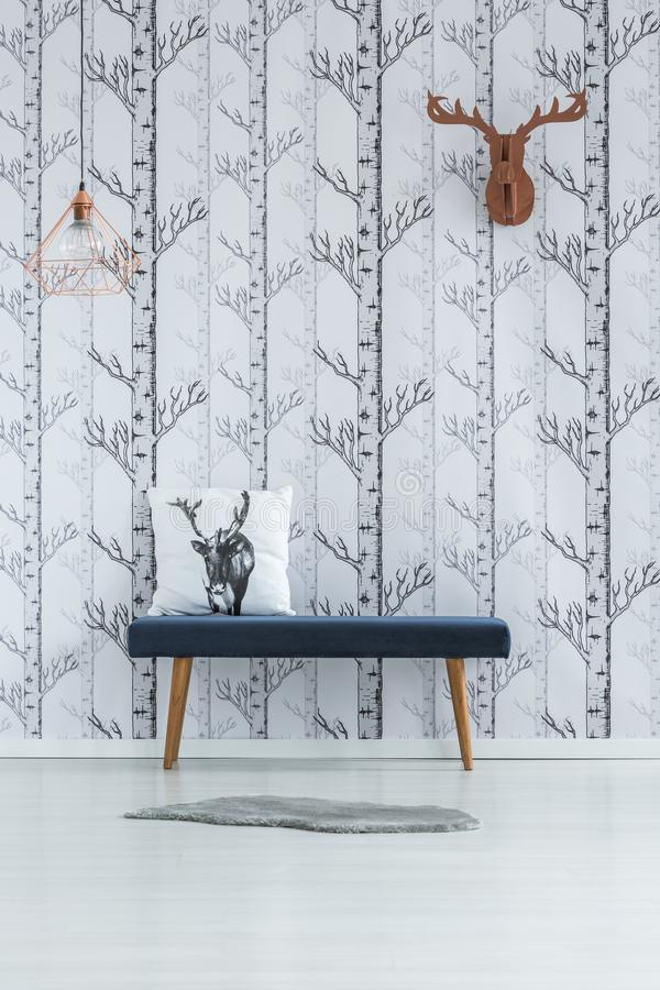 Room with trees wallpaper. Deer head on wall with trees wallpaper and pillow on stool in white room with fur on floor royalty free stock image