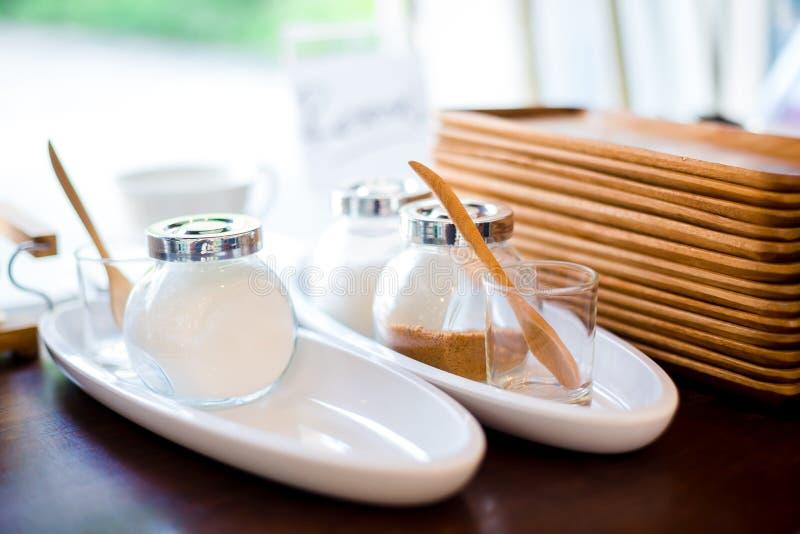 Room voor koffie met witte en rode suiker in een glaskruik met houten dienbladen op planken stock foto