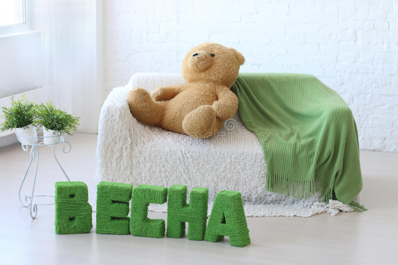 Room with white couch. Toy bear and green text on floor: Spring stock photography