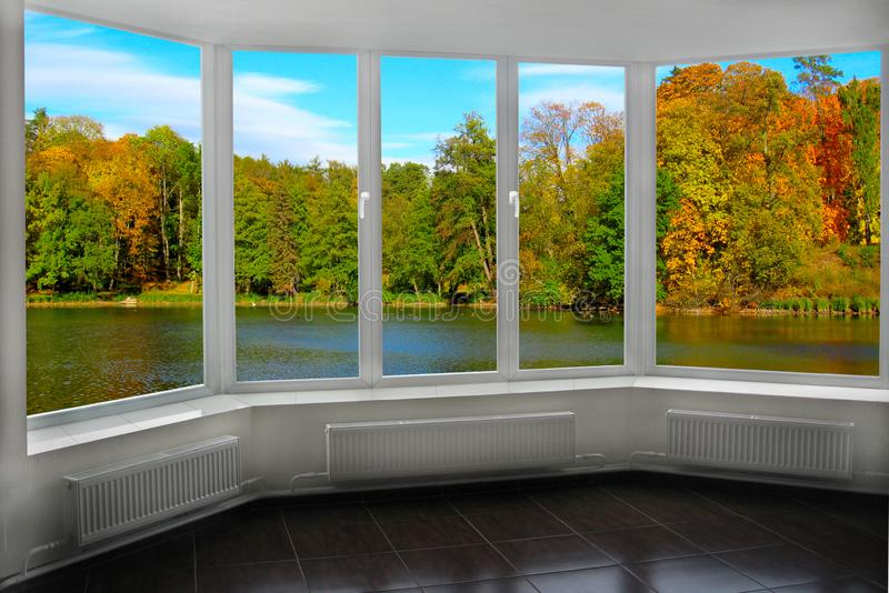Room with window with view to autumn forest and lake. Autumnal landscape. With lake in forest. Panoramic view to nature from room window. View from window to stock photos