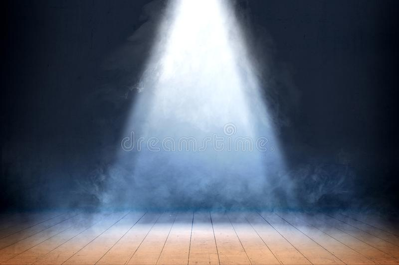 Room with wooden floor and smoke with light from the top. Against dark wall background royalty free stock photo