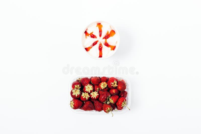 Roomijs met bovenste laagjestroop en een doos van verse aardbeien stock afbeeldingen