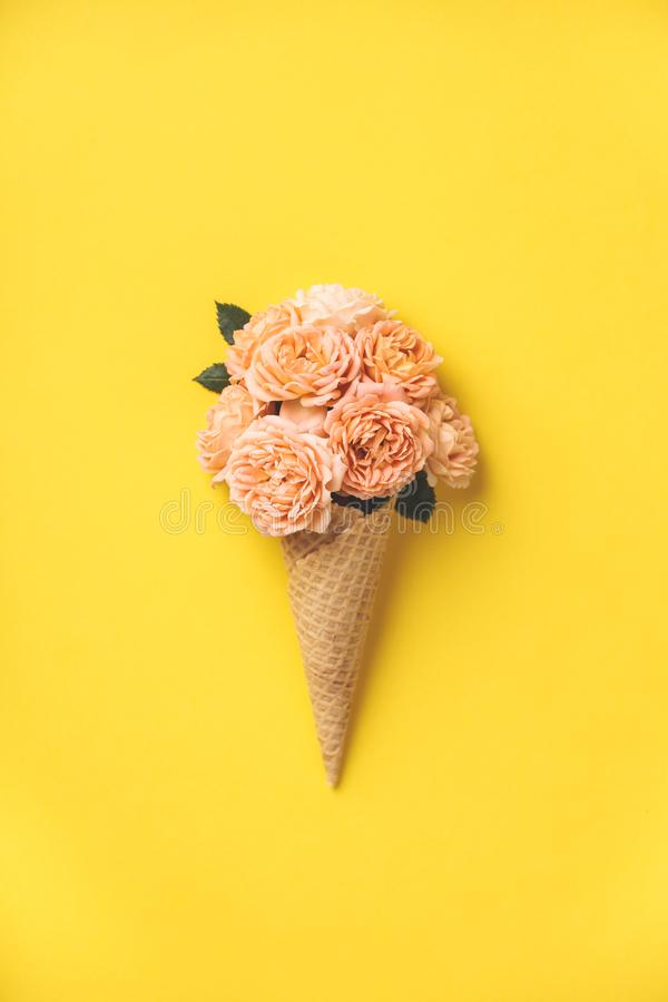 Roomijskegel met roze rozen op gele achtergrond stock foto's