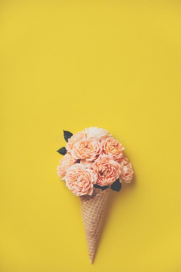 Roomijskegel met roze rozen op gele achtergrond stock fotografie