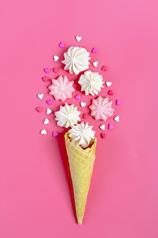 Roomijskegel met roze, witte schuimgebakjes en hart gevormd suikergoed op roze achtergrond stock foto