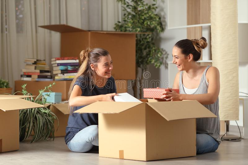 Roommates talking unboxing gelongings moving home stock photography