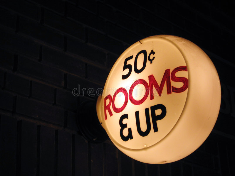 Rooms, 50 Cents & Up. This image depicts an old hotel sign lit up offering rooms for 50 cents stock photography