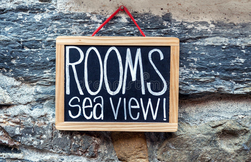 Rooms available sign. Rooms available chalkboard sign hanging on stone wall at a hotel royalty free stock photo