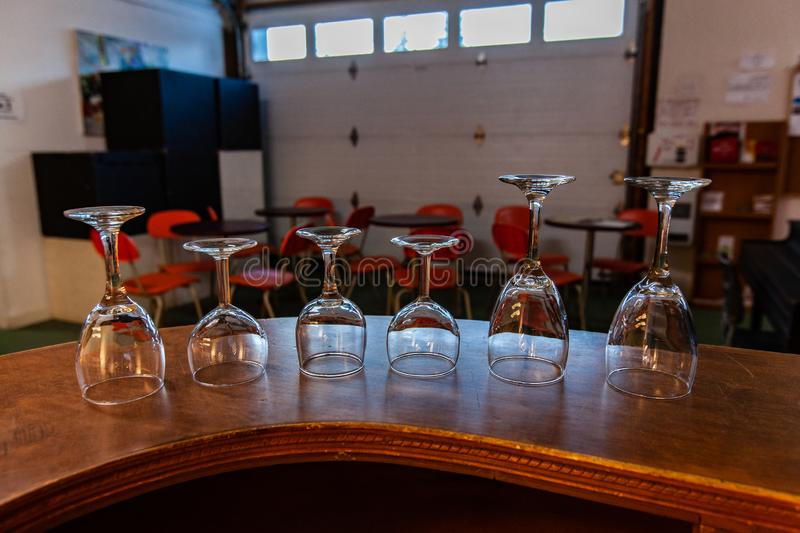Rooms for rent in community arts center. A close-up view of empty wineglasses stood upside down on a counter ready for use during a club gathering in a royalty free stock photography
