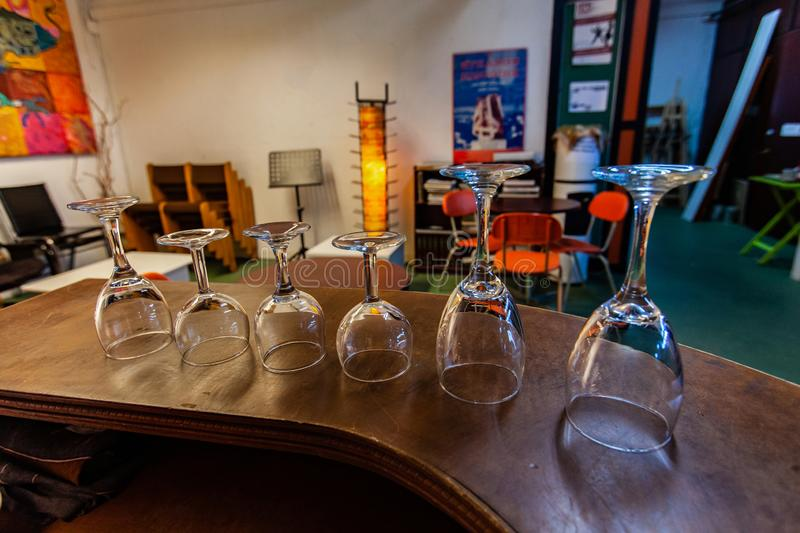 Rooms for rent in community arts center. A closeup view of stemmed glasses standing upside down on a bar inside a recreational building for local people. Blurry royalty free stock photo