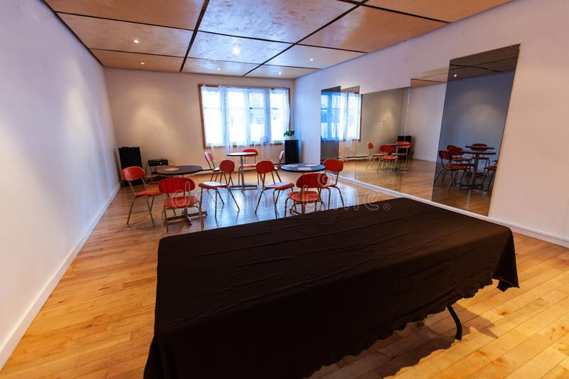 Rooms for rent in community arts center. An empty room is seen set out for a function. Tables and red seats are seen by tall mirrors inside a communal building royalty free stock image