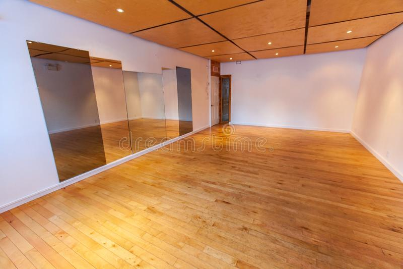 Rooms for rent in community arts center. A large angle view of a large recreational hall, with wood flooring and ceiling. Empty room with large mirrors stock photos
