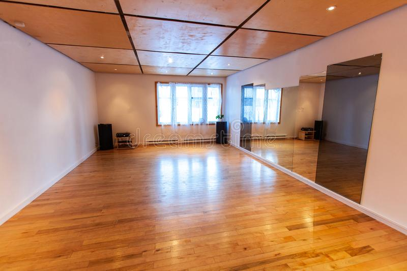 Rooms for rent in community arts center. A large and empty dance studio room with mirrored wall and wooden floor is seen inside a youth club building, wide stock photo