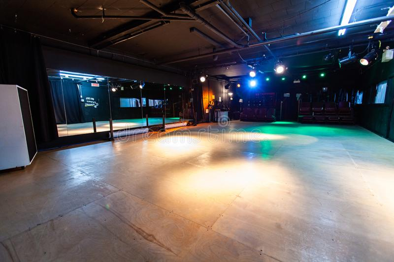 Rooms for rent in community arts center. A large hall used for dance practice is seen inside a recreational centre for local children. Artificially lit dance royalty free stock photos