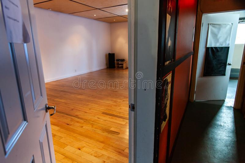 Rooms for rent in community arts center. An open door is seen close up inside a corridor, leading to a large recreational room inside a local youth club. Spaces stock images