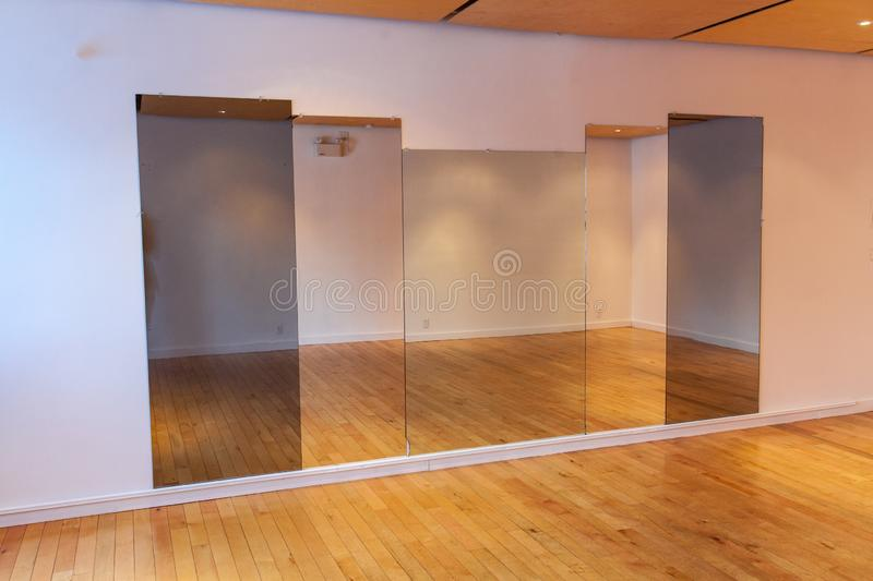 Rooms for rent in community arts center. Tall mirrors are seen hanging inside a deserted room. Recreation building with room available to hire, large space for royalty free stock photography