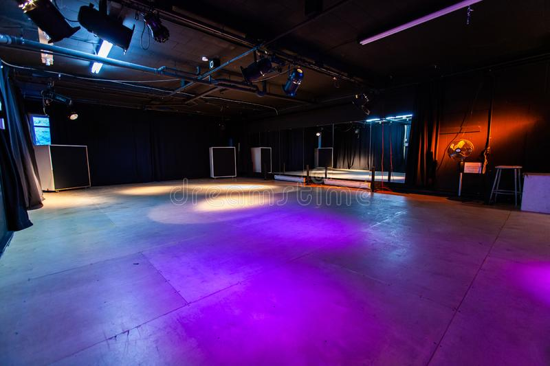 Rooms for rent in community arts center. A wide angle view of an empty dance studio with artificial stage lighting, violet lights shine down on a large royalty free stock photo