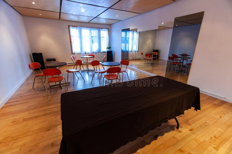 Rooms for rent in community arts center. A wide angle view inside a large multi-functional room. Empty tables and chairs are seen set out ready for a local club royalty free stock image