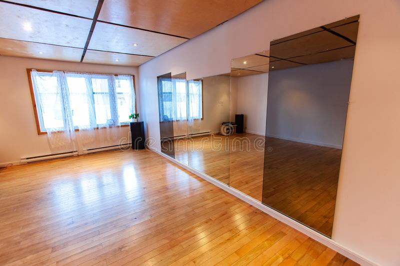 Rooms for rent in community arts center. A wide angled shot of an empty hall inside a local youth center. Pine flooring and large window are seen by mirrors stock photography