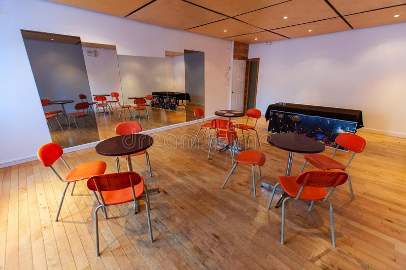 Rooms for rent in community arts center. A wide angled view of empty tables and chairs set out in a function room, on a wood floor by a mirrored wall. A large stock images