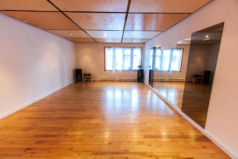 Rooms for rent in community arts center. A wide angled view of a large room with parquet flooring and mirrors hanging on the wall is seen inside a local royalty free stock photos