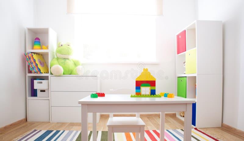 Rooom colorido das crianças com paredes e mobília brancas imagem de stock