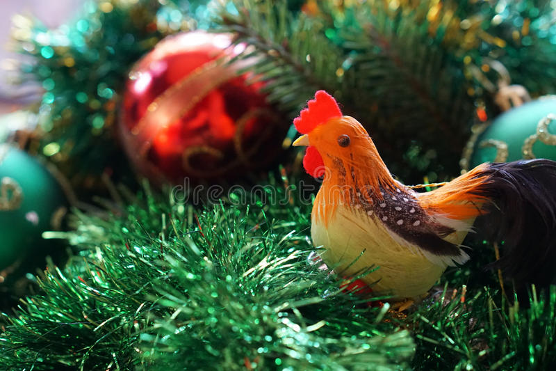Rooster on the background of Christmas tree royalty free stock image