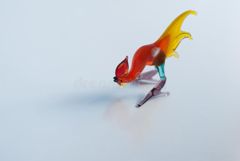 The rooster souvenir,. A Beautiful figurine made of colored glass on a white background, the symbol of 2017 royalty free stock image