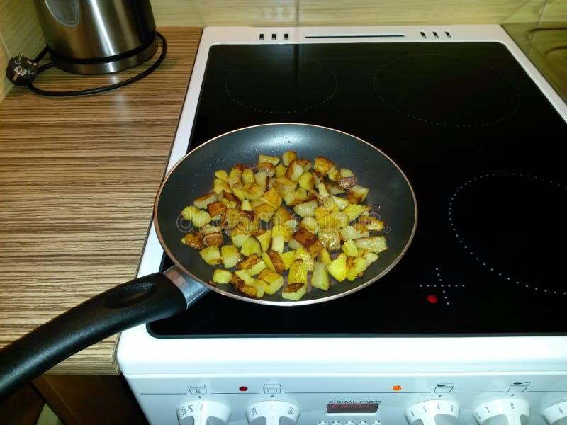 Roosterende aardappels op een pan, op een kooktoestel, op een ceramische haardplaat stock afbeeldingen