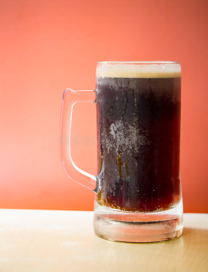 Root beer. Cold root beer on top of wooden table in front of orange background royalty free stock photos