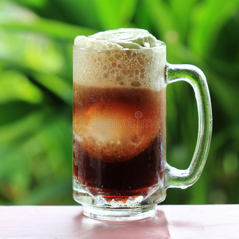 Root beer float. A tasty summer treat on Green tree background royalty free stock image