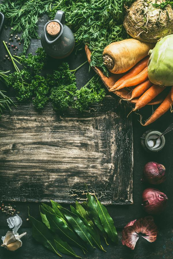 Root vegetables ingredients on dark kitchen table background with herbs and spices, top view. Copy space. Vegetarian cooking and royalty free stock photos