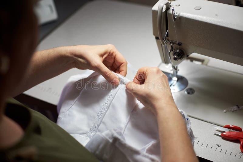 Ropa blanca que cubre de la modista con la aguja y sus manos Máquina de coser, tijeras en fondo Visión superior fotos de archivo