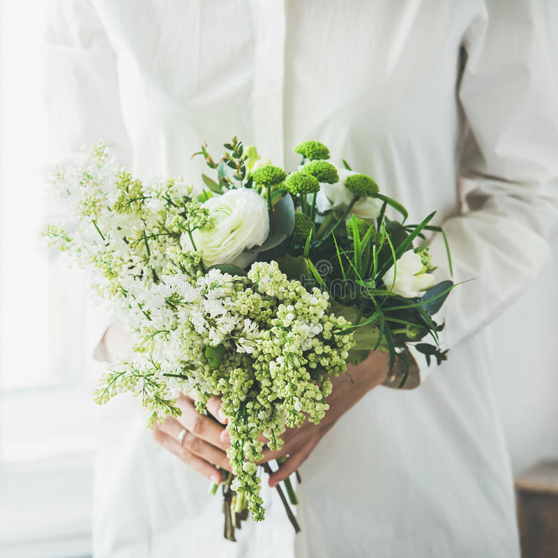 Ropa blanca que lleva de la mujer joven que sostiene el ramo de las flores, cosecha cuadrada foto de archivo libre de regalías